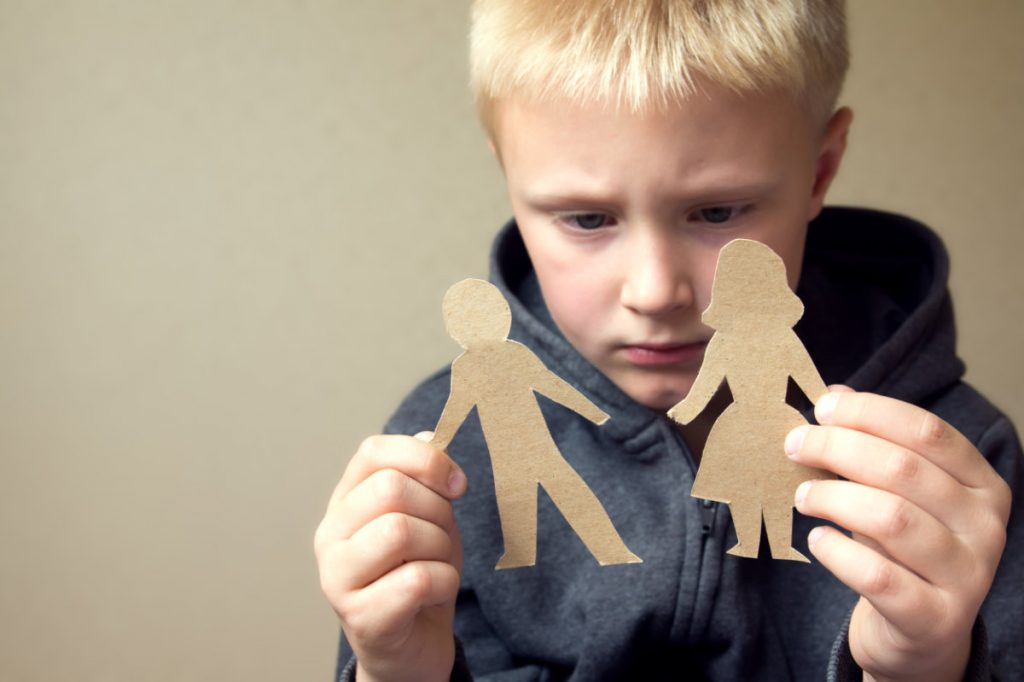 young child with paper dolls torn apart